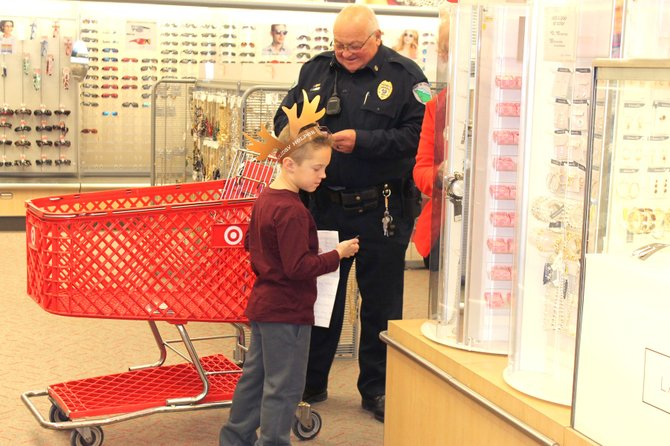 Cicero Police Officer John Fortino helps Ethan Bramoff, 6, pick out a gift at Target as part of the Shop with a Cop program Sunday, Dec. 1.
