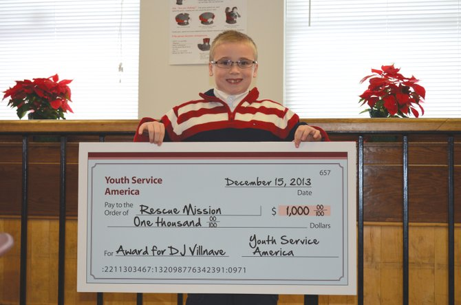 """Damon """"DJ"""" Villnave, 10, receives a Youth Services Agency grant for $1,000 for his efforts to help the Rescue Mission with his annual blanket drive, which he calls DJ's Gift of Warmth. The drive has collected more than 750 blankets since 2010. DJ hopes to collect 300 blankets this year. He donated the check to the Rescue Mission."""