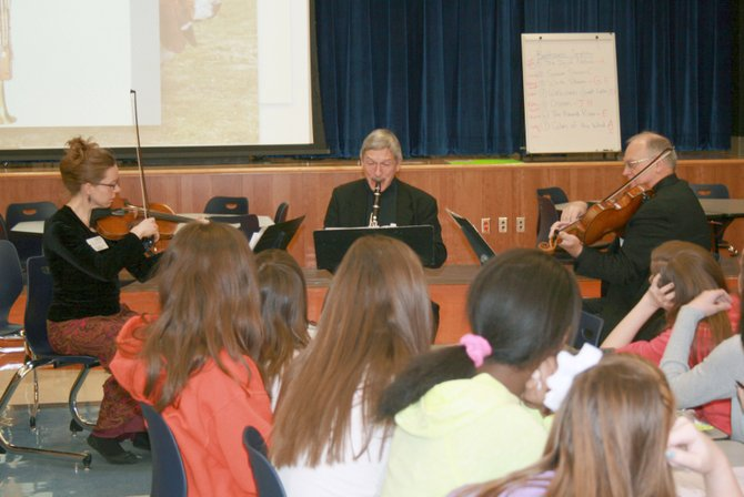 "The Liverpool Middle Orchestra has spent the past few weeks composing an ode to nature. The musical composition will make its debut during Symphoria's next Young Person's concert, ""Sounds of Nature,"" on March 1. Pictured, from left, are Symphoria members Sonya Williams, Allan Kolsky and Kit Dodd, who stopped by LMS to talk with the students about how to enhance their musical composition."