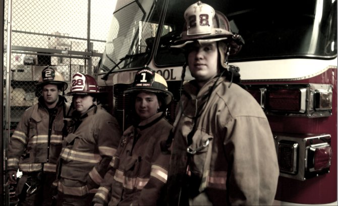 From left, Liverpool Firefiighter Corey Warren, Lieutenant Dave Ingram, bunk-in firefighter Nick Scoones and Captain John Laakso stand in front of the ladder truck at Station No. 1.