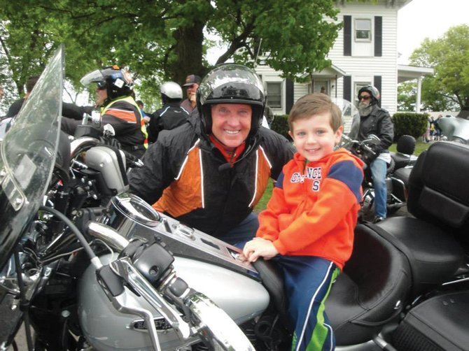 Rick Gary, one of the riders in Upstate Golisano Children's Hospital's Miracle Ride, poses with 6-year-old J.P. Mercer, a ride supporter. The ride raises money to support pediatric care at the hospital.