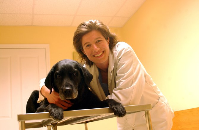 Dr. Tara Estra, owner of Canterbury Animal Hospital, with her 13-year-old Labrador, Vivi, who served as a brood dog for the Guiding Eyes seeing eye dog program. Canterbury is celebrating is fifth anniversary with an open house celebration on Saturday, Aug. 13. 