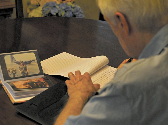 Pete McShane writes at home while his former self, a Green Beret medic, looks on.