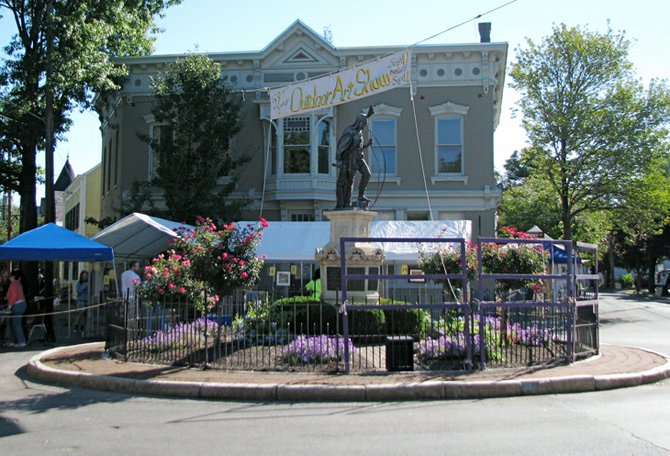 The statue of Lawrence the Indian serves as the center point of the Stockade Art Show, with the winning artwork displayed around it later in the day.
