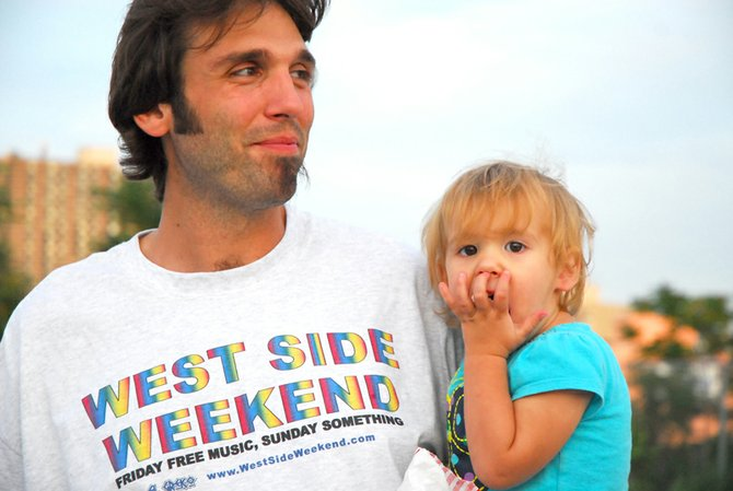 Demetrios Tsimis holds his 17-month-old daughter, Evangelina, at the Aug. 12 West Side Weekend event. The weekly community gatherings have been postponed until Tsimis can recruit more support, volunteers and interest.