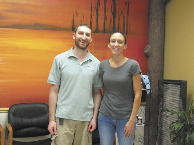 Eli Guterman, business owner, stands in the lobby of Back n' Touch in DeWitt with massage therapist Theresa Grosso. Grosso recently opened an all organic juice bar called Koinonia within the center.