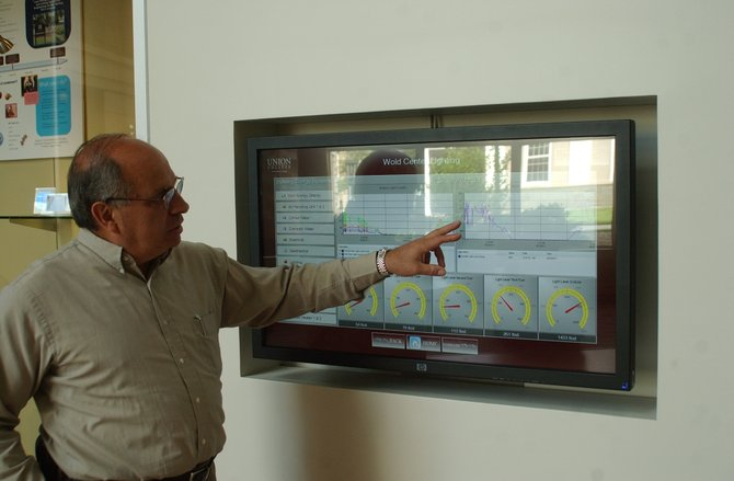 Frederick Puliafico shows off the touch screen display at Union Colleges new building, The Peter Irving Wold Center, which has extensive information on the buildings energy usage.