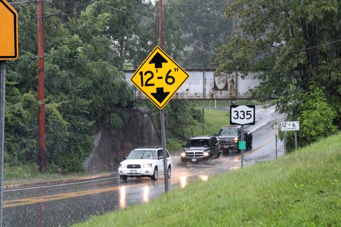 Motorists traverse standing water at the underpass on Elsmere Avenue Sunday morning, Aug. 28. 