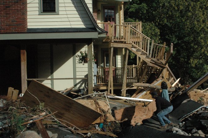 Owners look over the destruction of a home in Keene the morning after Tropical Irene came through the North Country Aug. 29, 2011.