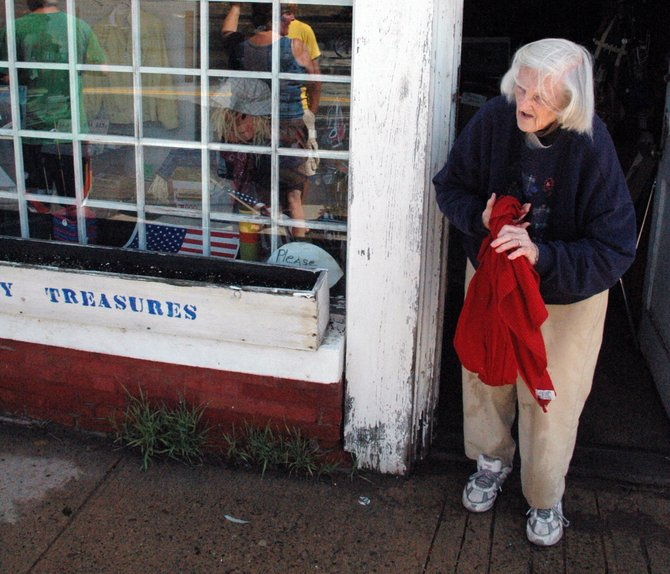 Bernice Shedd tries to dry out a blanket at Country Treasures in Willsboro, where water from the Boquet River flooded the Main Street area Aug. 29.