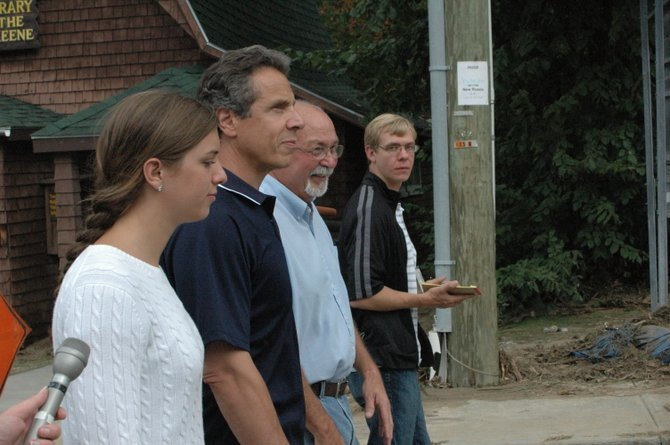 Gov. Andrew Cuomo and his daughter walk with Keene Supervisor William Ferebee as he tours the damage in Keene Aug. 30.