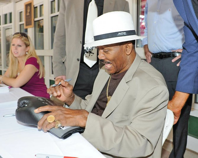 Former heavyweight champion Joe Frazier signs a boxing glove, during an autograph session at Saratoga Race Course on Friday, Aug. 26.
