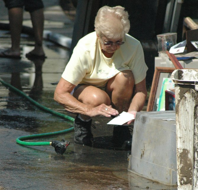 Veronica Murphy of Au Sable Forks washes off photographs recovered from her home.