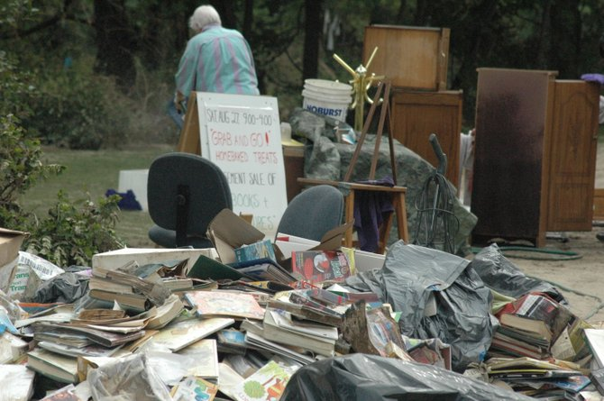 A pile of ruined books was created as volunteers helped to clean out the Wells Library in Upper Jay.