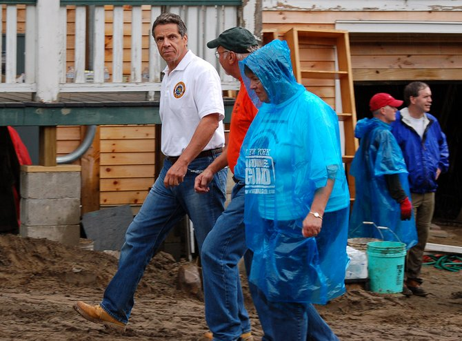 Gov. Andrew Cuomo tours storm-damaged homes and businesses in the Essex County town of Keene on Labor Day, Monday, Sept. 5, his second visit to this tiny Adirondack hamlet in a week. He met with government officials, volunteers and residents before talking to the media at the Keene firehouse, part of which was swept away in the Aug. 28 flash flood during Tropical Storm Irene. He is joined by Keene Supervisor William Ferebee (in orange) and Deputy Secretary of State for Local Government Dede Scozzafava (in blue).