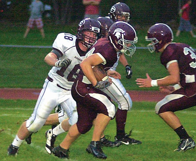 Burnt Hills-Ballston Lake's Jack Guba, center, eludes a Gloversville defender during last Friday's home opener.