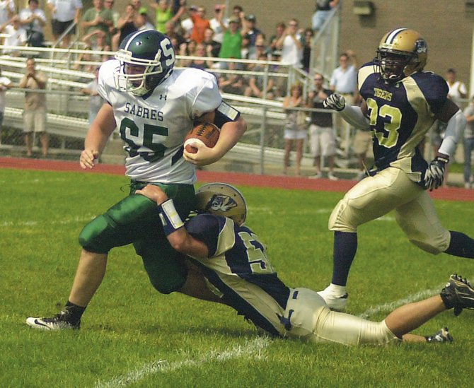 Schalmont's Marcus Ramundo (65) tries to elude a tackle as he returns a fumble recovery during last Saturday's season opener against Cohoes. The Sabres tamed the Tigers 41-7.