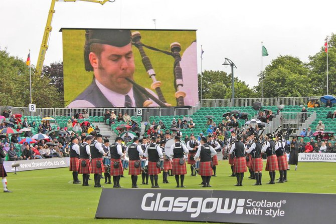 Andrew Douglas shows up on the video display during the World Pipe Band Championships.