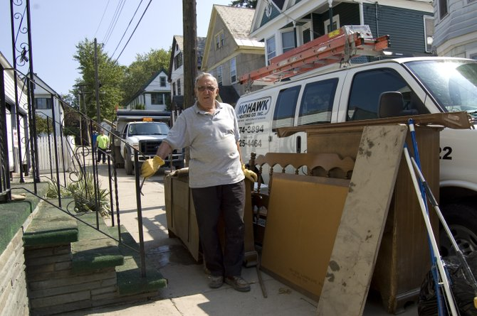 Peter Nicodemi, 73, an Ingersoll Avenue resident in the Stockade, stands outside the front of his home next to a pile of items damaged during the recent flooding.