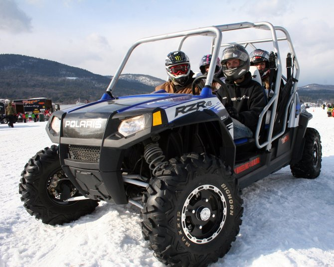 Dan Quaglieri gives a ride to a family in his RZR four-wheeler on Lake George