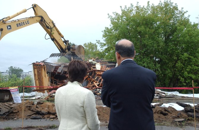 Albany International Airport CEO John O'Donnell and Colonie Supervisor Paula Mahan look on as a crane takes down two abandoned buildings left behind by a Park and Fly on Wednesday, Sept. 7.