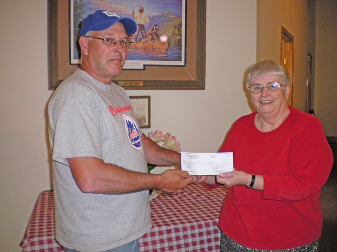 The Ticonderoga Knights of Columbus staged an Italian buffet for the benefit of the Ticonderoga Festival Guild, raising $1,030. Rollin Slattery, grand knight, presents a check to Cathie Burdick, guild executive director. The money supported a free concert by the Hague Jazz Quartet.