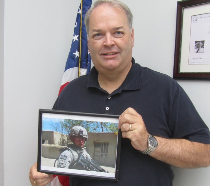 Town of Manlius assessor Pat Duffy holds a framed photo of his son, Matt, serving in Afghanistan. Matt, 23, is a combat engineer in the Army and is currently stationed at Fort Brag, N.C.
