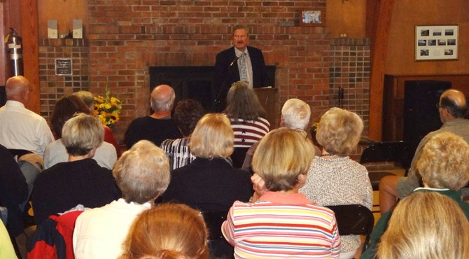 """Thomas Flynn, center,  reads an excerpt from his epic poem """"Bikeman"""" during a Cazenovia Forum sponsored event, Sept. 11 in the Presbyterian Church Meeting House."""