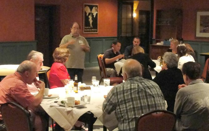 Greater Cazenovia Area Chamber of Commerce President, Gene Gissin, center, addresses about a dozen members in attendance at their Sept. 13 meeting in Les Pates et Les Nouilles.