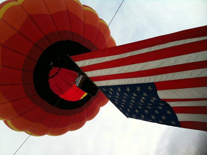 In a tribute to Adirondack Balloon Festival founder Walt Grishkot, balloonist John Outzen draped a giant American flag from his craft Thursday Sept. 22 during the opening ceremony of the 2011 festival. Outzen noted that for years, Grishkot loved this traditional patriotic salute.
