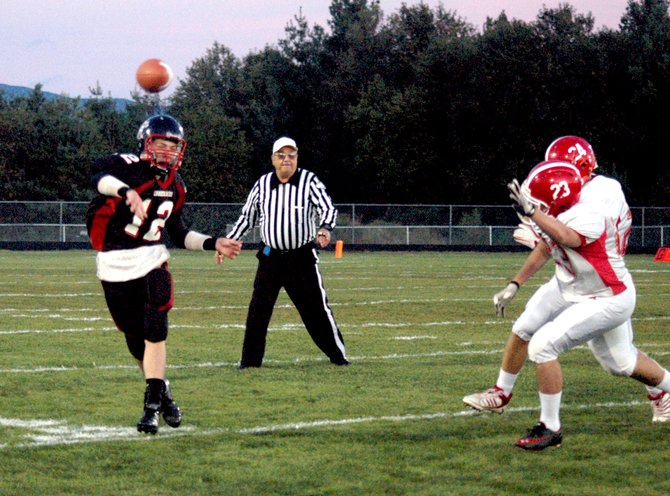 Tupper Lake quarterback Morgan Stevens throws as Saranac Lake defenders Lance Ackerson and Idriz Cecunjanin give chase.