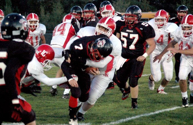 Tupper Lake running back Jordan Garrow tries to break through a Saranac Lake tackle.