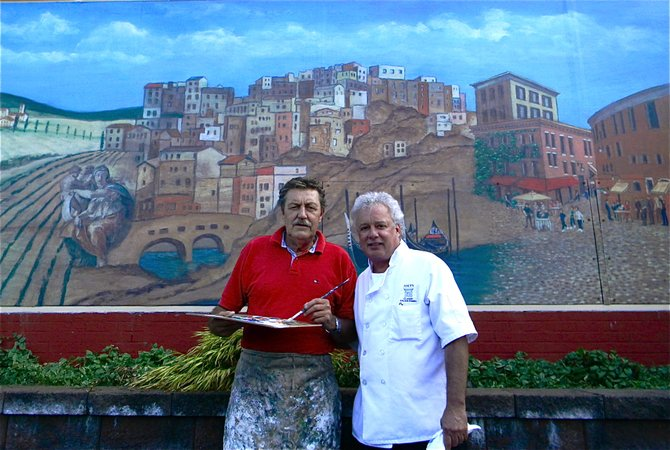 Cazenovia artist, Paul Parpard, left, takes a minute from putting the finishing touches on  his 25-foot mural outside of Joey's Classic Italian Restaurant, to pose for a photo with the owner, Joey DeCuffa.