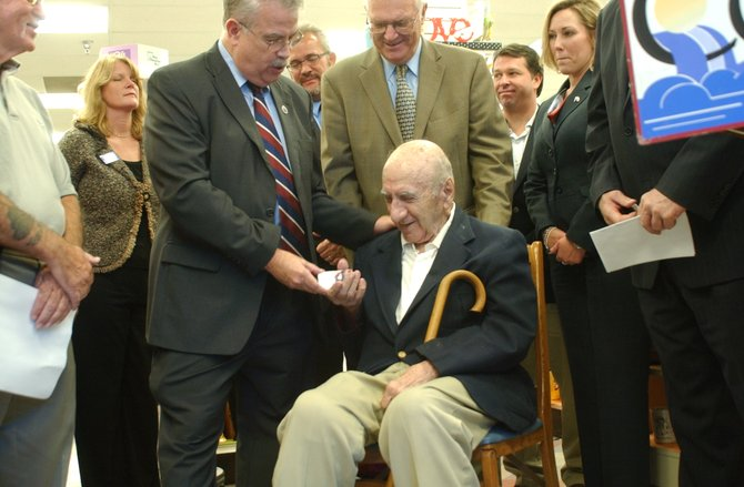 George Infante, a World War II veteran and former Albany County Legislator, receives his discount card for the Return the FAVOR Program, which was kicked off at Marra's Pharmacy in Cohoes on Tuesday, Sept. 20.