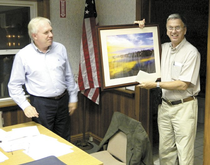 Jorge Batlle, right, accepts the gift of a Francis McCormick framed photo from Village Mayor Marty Hubbard, left, at the Sept. 22 village board meeting. The photo, as well as a $450 contribution to SAVES in Batlle&#39;s name, was given in recognition of Batlle&#39;s long career in public service to the village.