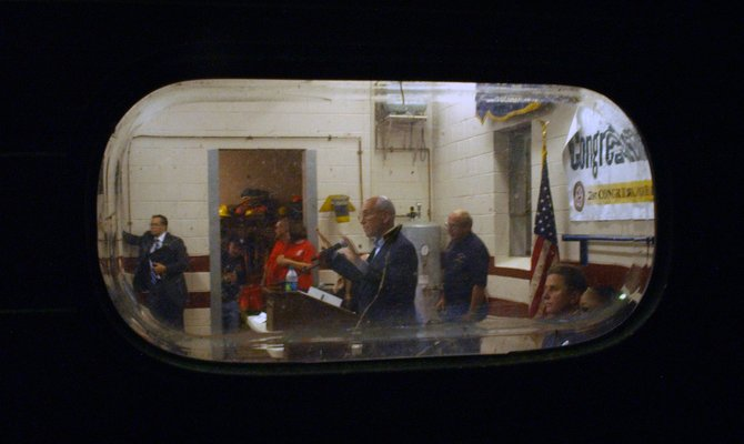 "Congressman Paul Tonko hosted a ""town hall"" style meeting at the Rotterdam Junction Fire Department on Wednesday, Sept. 28, with residents often sharing heated comments. Tonko addressed concerns well after sunset, as seen through a window on one of the department's garage doors."