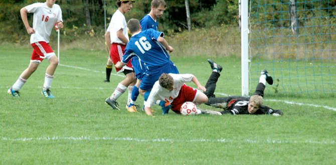 Saranac Lake goalie Ricky Schmidt and defender Jessie Ettinger try to get the ball out of the penalty are and away from Peru attackers, including Andrew Kneussle.