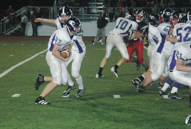 Nate Lenhart hands the ball off to Jay Hebert for Ticonderoga Sept. 30.