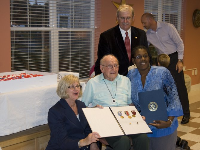 John Luczka, center, holds the medals he hadn't received after serving in the Navy during WWII until Thursday, Sept. 22. To Luczka's left is his niece Linda Novak, who pursued obtaining the medals, and to his right kneels Cora Schroeter, constituent representative from U.S. Rep. Paul Tonko's office.