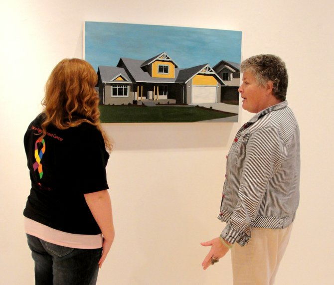 "Cazenovia College Reisman Hall Art Gallery Director Jen Pepper, right, discusses Sanders Watson's 2008 oil painting ""North Carolina,"" with junior photography major Brittany Hill. Watson's work was featured in the gallery's last exhibit ""Dwell,"" which concluded Oct. 2."