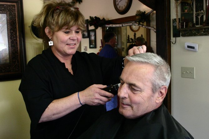 Heidi Baker, one of the first female barbers to establish a barber shop in the region, trims up Ron Haskell's hair this week. Baker's enterprise, Heidi's Clip Joint, moved recently to 3685 Main St. in Warrensburg to the log-sided building across from the local National Grid garage.