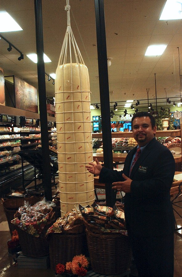 Augie Reyes, director of deli and prepared foods for ShopRite, poses next to the log of provolone cheese hanging in the new supermarket in Niskayuna.