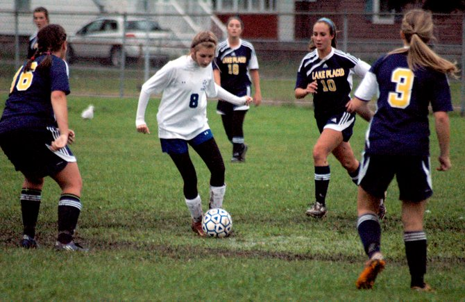 Peyton Falb of Seton Catholic dribbles through a host of Lake Placid defenders.