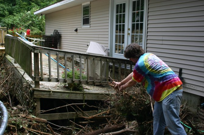 Just hours after floodwaters Kris and Kathie Erceg's home was swept off its foundation by Tropical Storm Irene, their son Nick yanks at some debris that slammed against the house, which was later condemned. A fundraiser party is being held from noon to 9 p.m. Saturday Oct. 15 to raise money to help the family relocate after the devastating loss — insurance did not cover the destruction.