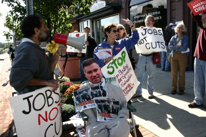 Protest rally organizers Joe Seemen (at bullhorn) and Susan Weber (center, rear) lead a chant of 'Jobs, Not Cuts' in front of the Glens Falls office of U.S. Rep Chris Gibson, who they said was following failed economic policies that enrich the wealthy while squeezing the finances of the middle class and the poor. Gibson representatives welcomed the protest, while declaring that Gibson is taking action to advocate for job development and equality in taxation.