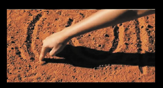 "In this still frame from ""Burrulaa,"" indiginous tour guide Renata explains and demonstrates the earliest form of Australian artwork, ground sand paintings. Here, she is showing the  representation for 'male': the 'U' shape for a human bottom, a line on the right representaing a spear, and a curved line on the left representing a boomerang."