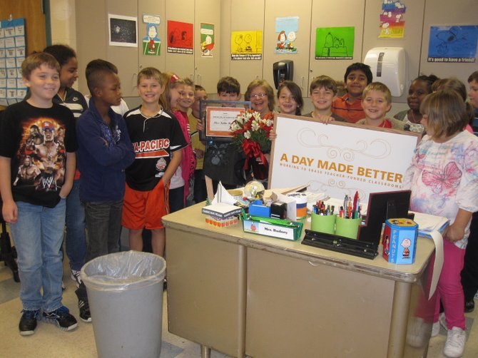 """Forest Park Elementary School teacher Kelli Budney is surrounded by her class after receiving $2,000 worth of school supplies from an Office Max located on Central Avenue for its """"A Day Made Better"""" program."""