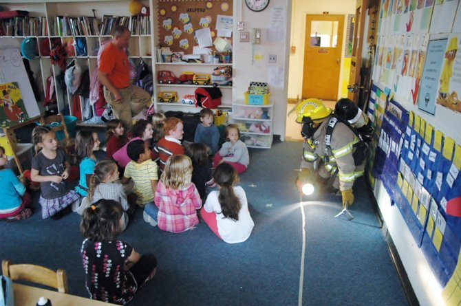 Lyle Fielder crawls into the Westport Central School kindergarten class to show students what a firefighter looks like when searching a house.