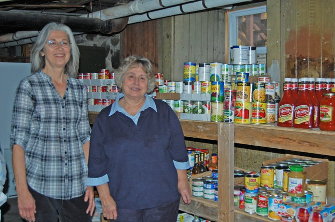 Diane Redman, food pantry volunteer, and Sue Morse, food pantry manager, stock freshly donated non-perishable food items in the Moriah Food Pantry. The pantry is located in the basement of All Saint's Church in Mineville.
