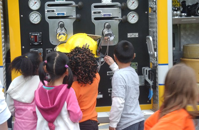 Firefighters Bryan Natoli and Joe Laughlin, show Bought Hills Elementary students a fire truck Thursday, Oct. 13.